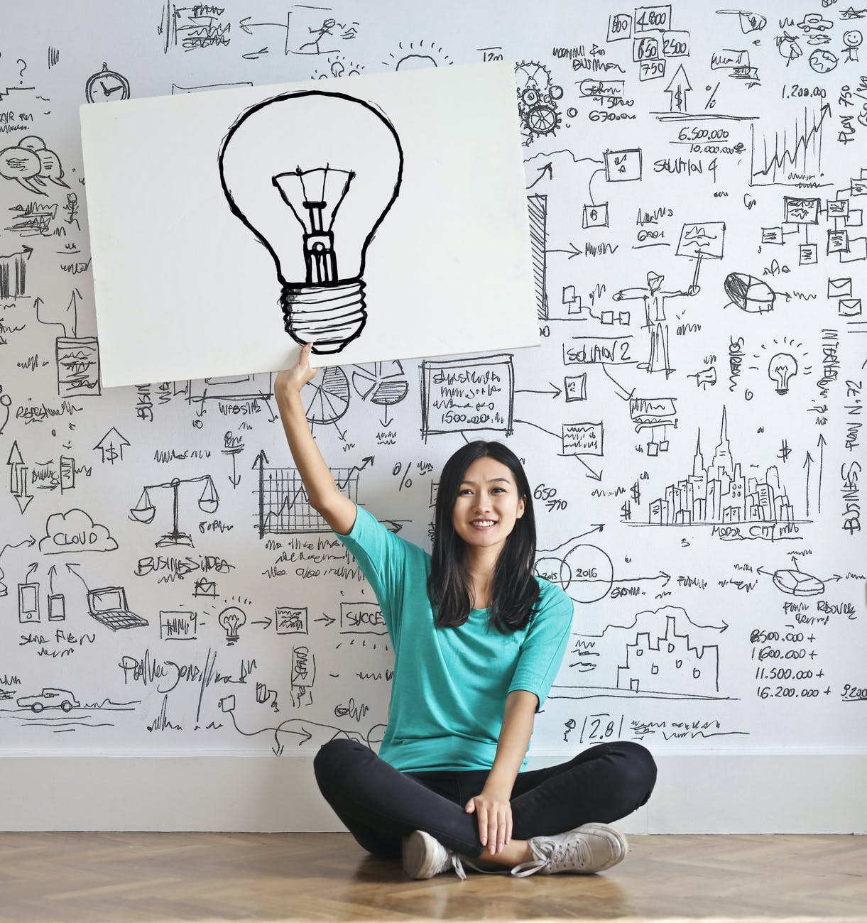 woman draw a light bulb in white board