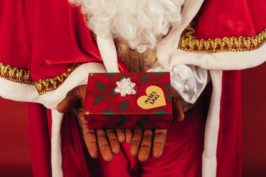 person wearing santa claus outfit while holding christmas gift
